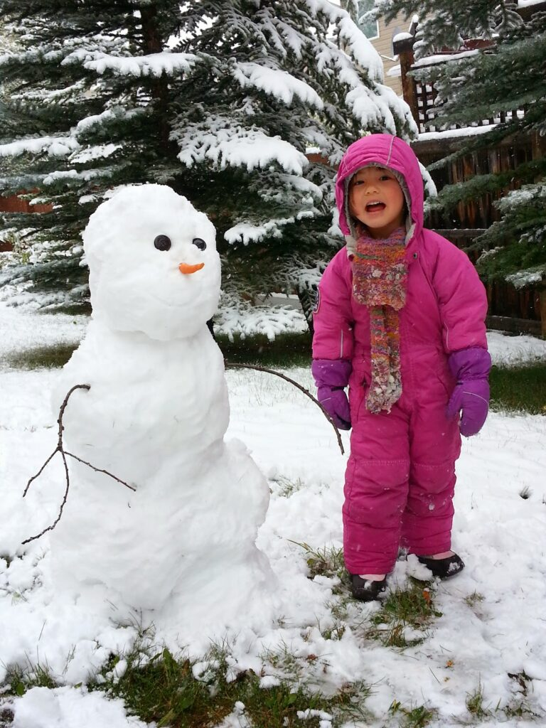 Young girl and snowman